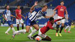 Striker Manchester United, Marcus Rashford, berebut bola dengan pemain Brighton pada laga Premier League pekan ke-32 di Stadion Falmer, Rabu (1/7/2020) dini hari WIB. Manchester United menang 3-0 atas Brighton. (AFP/Andy Rain/pool)