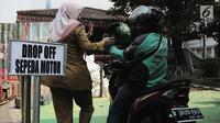 Pengemudi ojek online menaikkan penumpang di tempat drop off yang disediakan di Balai Kota DKI Jakarta, Selasa (31/7). Pengemudi ojek online harus menempati area tersebut saat menunggu penumpang. (Liputan.com/Faizal Fanani)