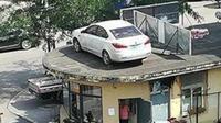 Sebuah mobil terlihat parkir di tempat tak biasa, yaitu di atap pos security, di Benxi, Lianing, China. (South China Morning Post)