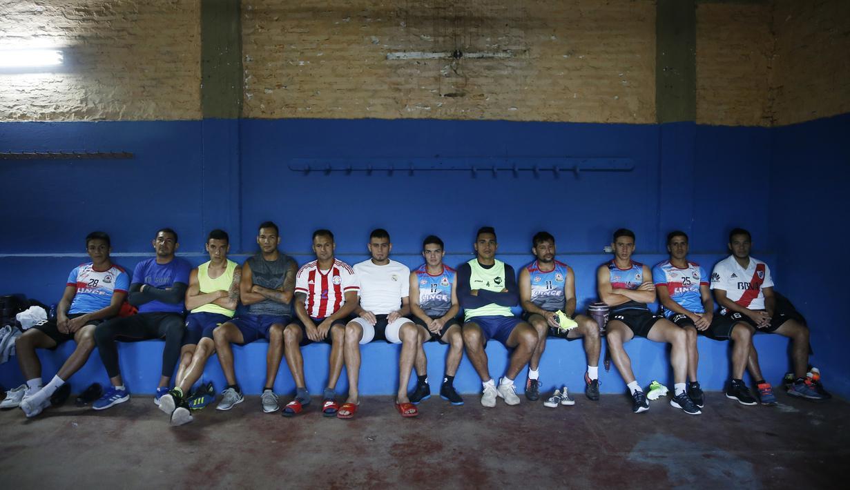 Striker klub divisi dua Resistencia, Nicolas Caballero (keempat kanan) beristirahat di ruang ganti klub di Paraguay, 2 Februari 2021. Caballero (32) yang lebih dari setahun belum dibayar oleh klub, kini memiliki kios barbekyu di pinggir jalan untuk bertahan hidup selama pandemi. (AP/Jorge Saenz)