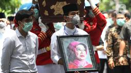 Putra Presiden Joko Widodo, Gibran Rakabuming Raka (kanan) serta adiknya Kaesang Pangarep membawa foto sang nenek Sudjiatmi Notomihardjo saat akan disalatkan di masjid dekat kediamannya di Solo, Jawa Tengah, Kamis (26/3/2020). Ibunda Jokowi meninggal karena sakit kanker. (Liputan6.com/Fajar Abrori)
