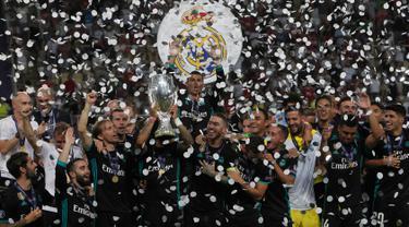 Pemain Real Madrid mengangkat trofi Piala Super Eropa usai menumbangkan Manchester United (MU) 2-1 di Skopje, Macedonia, Selasa (8/8). Ini merupakan gelar Piala Super Eropa keempat bagi Real Madrid. (AP Photo/Boris Grdanoski)