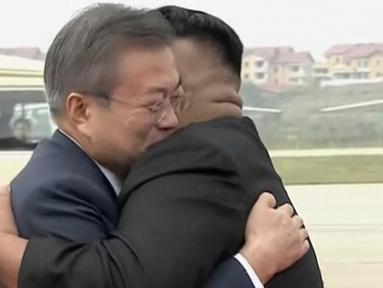 Presiden Korea Selatan, Moon Jae-in (kiri) memeluk pemimpin Korea Utara, Kim Jong-un setibanya di Pyongyang, Selasa (18/8). Kedatangan Moon Jae-in ke negara tersebut adalah untuk pertemuan ketiga dengan Kim Jong-un. (Korea Broadcasting System via AP)