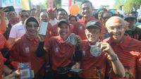 Menteri BUMN RI Rini M Soemarno (tengah) menunjukkan aplikasi pembayaran digital LinkAja yang digunakan oleh para finisher untuk mendapatkan medali BNI ITB Ultra Maraton 2019 di Kampus ITB, Bandung, Minggu (13 Oktober 2019).