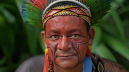 Seorang pria bernama Garapira dari suku Pataxo berpose untuk difoto di Rio de Janeiro, Brasil (14/4). Brasil merayakan Indian Day yang digelar setiap tanggal 19 April untuk menghormati masyarakat adat dan budaya setempat. (AFP/Carl De Souza)