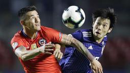 Gelandang Chili, Charles Aranguiz, duel udara dengan gelandang Jepang, Shoya Nakajima, pada laga Copa America 2019 di Stadion Morumbi, Selasa (18/7). Chili menang 4-0 atas Jepang. (AP/Andre Penner)