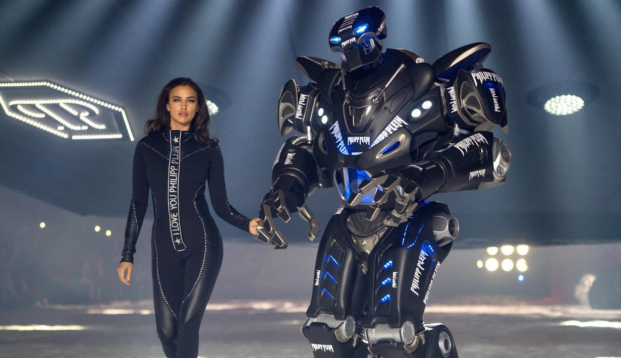 Model Irina Shayk melenggang ditemani robot sambil membawakan koleksi desainer Philipp Plein dalam New York Fashion Week 2018, Sabtu (10/2). Robot warna hitam yang bentuknya menyerupai Transformers itu lalu berjalan di sepanjang catwalk  (AP/Craig Ruttle)