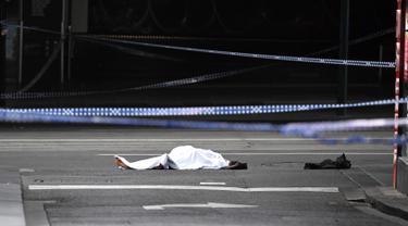 Sesosok jasad terbungkus kain putih terlihat setelah insiden penikaman di Melbourne, Australia, Jumat (9/11). Penikaman terhadap pejalan kaki tersebut diduga dilakukan oleh anggota teroris. (WILLIAM BARAT/AFP)