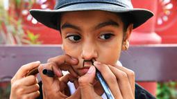Seorang anak dirias selama memperingati ulang tahun Charlie Chaplin di Adipur, India (16/4). Ratusan pengemar Charlie Chaplin mengenakan topi bowler dan kumis palsu membawa tongkat berjalan merayakan aktor komik tersebut. (AFP Photo/Indranil Mukherjee)
