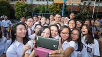 Gubernur DKI Jakarta Basuki Tjahaja Purnama selfie bersama siswa SMA Negeri 2, Jakarta, Selasa (14/4/2015). (Liputan6.com/ Faizal Fanani)