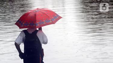 Warga melihat Jalan Di Panjaitan dekat Halte Transjakarta Cawang Soetoyo yang tergenang banjir, Jakarta, Rabu (1/1/2020). Hujan yang mengguyur Jakarta sejak Selasa sore (31/12/2019) mengakibatkan banjir di sejumlah titik di Jakarta. (Liputan6.com/Helmi Fithriansyah)