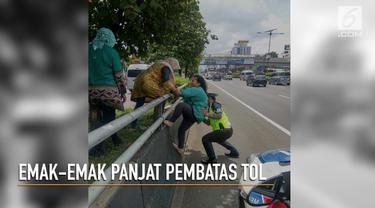 Diturunkan di pinggir tol, emak-emak ini dibantu polisi untuk memanjat pembatas tol yang tinggi.