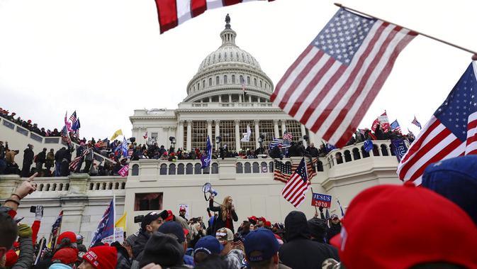 Massa pendukung Presiden Amerika Serikat Donald Trump berkumpul di luar Capitol Hill, Washington, Amerika Serikat, Rabu (6/1/2021). Sejumlah anggota parlemen dan massa pendukung Donald Trump menyerbu Capitol Hill untuk membatalkan pemilihan presiden Amerika Serikat. (AP Photo/Shafkat Anowar)