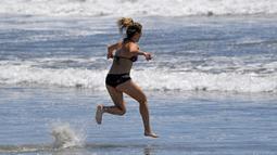 Seorang wanita berlari di Pantai Venice, Los Angeles (13/5/2020). Los Angeles County membuka kembali pantai-pantainya pada Rabu dalam pelonggaran terbaru pembatasan coronavirus yang telah menutup sebagian besar ruang publik dan bisnis California selama hampir dua bulan. (AP/Mark J. Terrill)