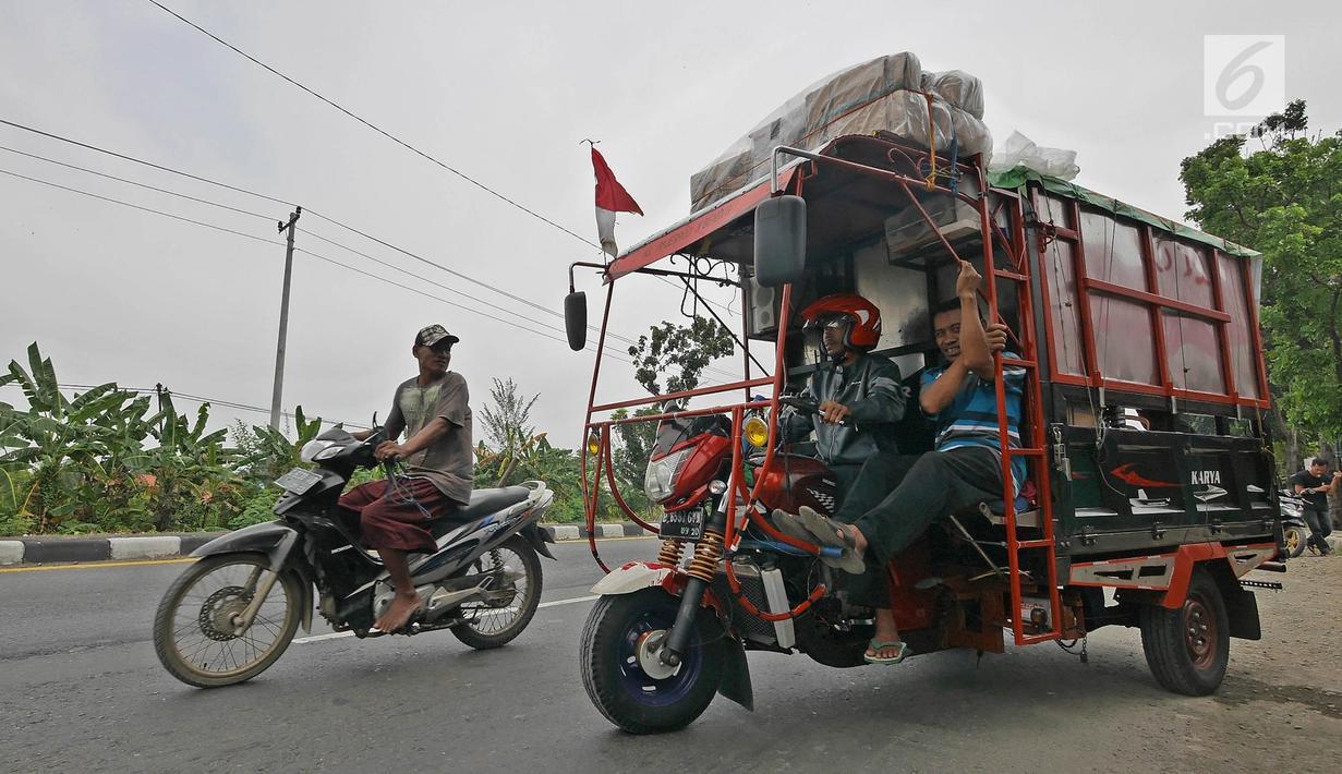 Pemudik bersama keluarganya menggunakan motor bak roda tiga bersiap kembali melakukan perjalanan mudik di Jalur Pantura kawasan Pemalang, Jawa Tengah, Senin (3/6/2019). Keluarga ini sudah sejak tiga tahun lalu menggunakan motor bak roda tiga untuk mudik. (Liputan6.com/Herman Zakharia)