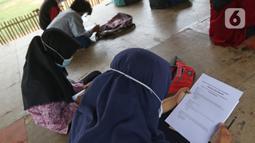 Seorang murid SMP Sekolah Alam melihat soal Ujian Akhir Semester (UAS) di Sukawangi, Kabuapaten Bekasi, Jawa Barat, Senin (30/11/2020). Menurut pengurus Sekolah Alam KBM tatap muka  jenjang pendidikan SD,SMP, dan SMA tetap berjalan dengan menerapkan protokol kesehatan. (Liputan6.com/Herman Zakharia)