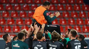 Pemain Werder Bremen merayakan keberhasilan bertahan di kompetisi Bundesliga usai menahan imbang Heidenheim 1846 di laga play-off leg kedua, Selasa (7/7/2020) dini hari WIB. Bremen bermain imbang 2-2 atas Heidenheim. (AFP/Kai Pfaffenbach/pool)