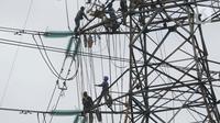 Pekerja menyelesaikan pekerjaan jaringan SUTET di Tangerang, Banten, Senin (2/1/2021). PT PLN (Persero) memiliki pasukan khusus yang terlatih melakukan pemeliharaan, perbaikan, dan penggantian perangkat isolator, konduktor maupun komponen lainnya pada jaringan listrik. (Liputan6.com/Angga Yuniar)