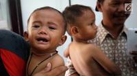 Anak balita menangis saat ditimbang di Puskesmas, Kaduhejo, Pandeglang (14/9). Dengan puluhan penduduk mengalami gizi kurang, gizi buruk dan beberapa anak sudah divonis stunting, ini menjadi gambaran bagaimana sulitnya mencegah stunting. (Foto:Istimewa)