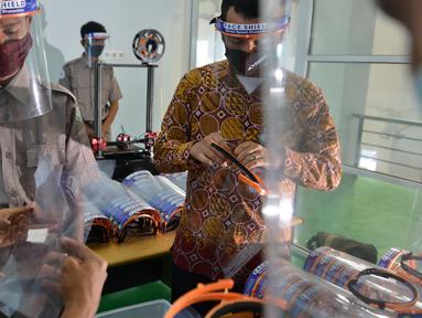 Siswa Sekolah Menengah Kejuruan memproduksi alat pelindung wajah (face shield) di Banda Aceh, Aceh, Jumat (12/6/2020). Selain memproduksi alat pelindung wajah, mereka juga membuat hand sanitizer yang akan disumbangkan untuk tenaga medis penanganan COVID-19. (CHAIDEER MAHYUDDIN/AFP)