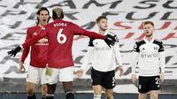 Striker Manchester United, Edinson Cavani, merayakan gol bersama Paul Pogba ke gawang Fulham pada laga Liga Inggris di Stadion Craven Cottage, Rabu (20/1/2021). MU menang dengan skor 1-2. (Peter Cziborra/Pool via AP)