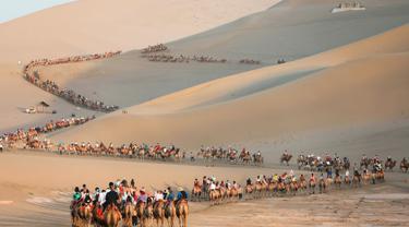 Para wisatawan menaiki unta di padang pasir di Dunhuang di provinsi Gansu di China barat laut (10/8/2019). Dunhuang adalah sebuah kota tingkat kabupaten di barat laut provinsi Gansu, Tiongkok Barat. (AFP Photo/Str)