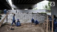 Pekerja Sudin Sumber Daya Air Jakpus menyelesaikan penutupan lubang rembesan di Tanggul Kanal Banjir Barat, Latuharhari, Minggu (5/1/2020). Penutupan untuk mengantisipasi tanggul jebol setelah diketahui terdapat rembesan di sejumlah titik akibat debit air KBB meningkat. (merdeka.com/Iqbal Nugroho)