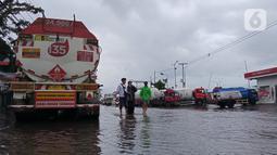 Warga menerobos banjir yang menggenangi daerah Kaligawe, Kota Semarang, Selasa (9/2/2021). Banjir dengan ketinggian 30 hingga 90 cm ini melumpuhkan akses Semarang ke Demak dan sebaliknya. (Liputan6.com/Gholib)