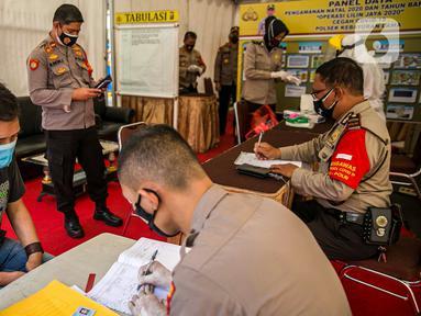 Polisi mendata warga saat rapid test gratis di Pos Pengamanan Natal 2020 dan Tahun Baru 2021 Polsek Kebayoran Lama, Jakarta, Selasa (29/12/2020). Rapid test itu dilakukan untuk membantu mengurai antrean warga saat tes di tempat lainnya. (Liputan6.com/Faizal Fanani)