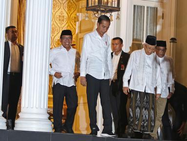 Pasangan capres-cawapres nomor urut 01 Joko Widodo (kiri) dan Ma'ruf Amin menghampiri wartawan di kediaman Ma'ruf Amin, Jalan Situbondo, Menteng, Jakarta, Kamis (27/6/2019). Jokowi menjemput Ma'ruf untuk nonton bareng sidang putusan MK di Lanud Halim Perdanakusuma. (Liputan6.com/Herman Zakharia)