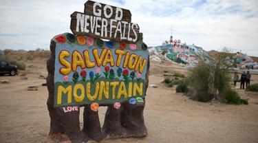 Sebuah tanda yang menandai pintu masuk ke Salvation Mountain, sebuah lereng bukti di Niland, California, Amerika Serikat. Dibuat oleh penduduk lokal bernama Leonard Knight, Salvation diisi dengan banyak seni lukis berupa mural dengan kutipan Kristen dan ayat-ayat Alkitab. (Robyn Beck/AFP)