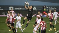 Kiper Athletic Bilbao, Unai Simon (tengah) menangkap bola dari ancaman pemain Real Madrid dalam laga semifinal Piala Super Spanyol 2020/21 di La Rosaleda Stadium, Malaga, Kamis (14/1/2021). Athletic Bilbao menang 2-1 atas Real Madrid. (AFP/Jorge Guerrero)