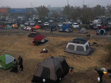 Sejumlah tenda terpasang di kamp pengungsian di sebuah lapangan di samping tempat parkir Walmart, Chico, California, AS (16/11). Akibat kebakaran yang terjadi di California sekitar 63 orang tewas. (AFP Photo/Justin Sullivan)