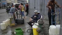 Warga memanfaatkan hidran kebakaran untuk mengisi wadah mereka dengan air di lingkungan San Juan di Caracas, Venezuela (19/1/2021). Venezuela merupakan negara dengan salah satu cadangan minyak terbesar di dunia. (AP Photo/Matias Delacroix)