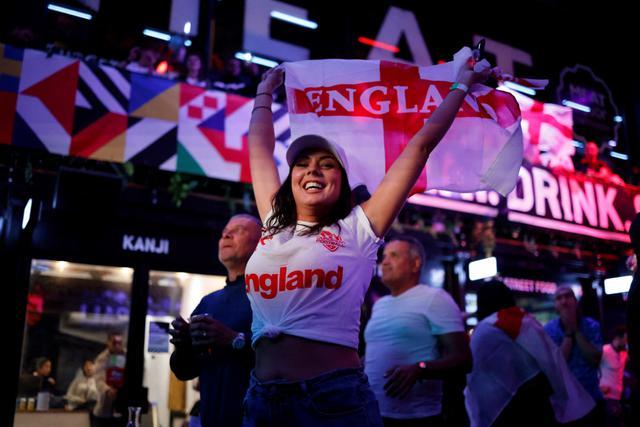 Pendukung Inggris merayakan kemenangan usai peluit akhir dibunyikan  pada pertandingan semifinal EURO 2020 antara Inggris dan Denmark, di Boxpark Croydon di London selatan (8/7/2021). Inggris menang atas Denmark dengan skor 2-1. (AFP/Tolga Akmen)