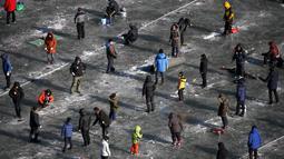 Sejumlah warga berusaha mendapatkan ikan air tawar melalui lubang kecil selama acara Festival Es di sungai yang beku di Hwacheon, selatan dari zona demiliterisasi (DMZ) yang memisahkan dua Korea, (9/1/2016). (REUTERS/Kim Hong-Ji)