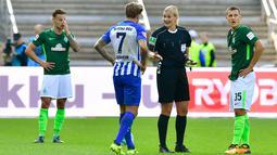 Wasit, Bibiana Steinhaus berdebat dengan gelandang Hertha Berlin, Alexander Esswein dan gelandang Werder Bremen, Maximilian Eggestein saat pertandingan Bundesliga Jerman di Berlin (10/9). (AFP Photo/Tobias Schwarz)