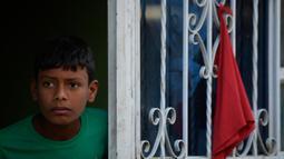 Anak laki-laki memandang ke luar jendela dengan kain merah yang menggantung untuk meminta bantuan makanan selama lockdown di Soacha, dekat Bogota, 4 April 2020. Presiden Kolombia Ivan Duque menetapkan lockdown dari 24 Maret lalu sebagai langkah mencegah penyebaran virus corona. (Raul ARBOLEDA/AFP)