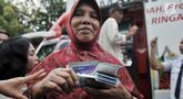 Warga seusai mengambil uang Kartu Lansia Jakarta (KLJ) melalui ATM Bank DKI di Jakarta Islamic Center, Koja, Rabu (24/4). Penerima KLJ mendapatkan Rp 600.000 per bulan sebagai bentuk pemberian bantuan sosial untuk pemenuhan kebutuhan dasar bagi lanjut usia. (merdeka.com/Iqbal S. Nugroho)