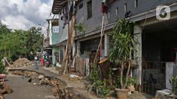Seorang pria mengambil gambar ruas jalan yang ambles di Jalan Kesatria, Matraman, Jakarta, Selasa (3/3/2020). Amblesnya ruas jalan mengakibatkan akses lalu lintas lumpuh total dan tidak bisa dilewati kendaraan roda dua maupun roda empat. (Liputan6.com/Herman Zakharia)
