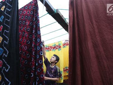 Pekerja menjemur kain sasirangan di kawasan Banjarmasin, Kalimantan Selatan, Senin (26/3). Kain sasirangan ini merupakan kain adat suku Banjar di Kalimantan Selatan. (Liputan6.com/Immanuel Antonius)