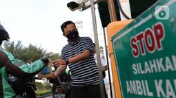Petugas membagikan takjil dengan sistem drive thru di Masjid Agung Al-Azhar, Jakarta, Selasa (5/5/2020). Selama Ramadan, pengurus Masjid Agung Al-Azhar membagikan 300 takjil per hari buat pengendara yang melintasi lokasi tersebut. (Liputan6.com/Helmi Fithriansyah)