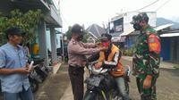 Nampak petugas TNI - Polres Garut, tengah memberikan masker kepada masyarakat saat pelaksaan operasi yustisi pencegahan Covid-19 di Garut, Jawa Barat. (Liputan6.com/Jayadi Supriadin)