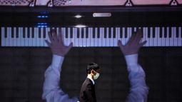 "Seorang pria berjalan melewati layar yang menampilkan pianis Nobuyuki Tsujii bermain selama konser ""The Pianist Special"", bermain di dalam ruangan dan secara bersamaan disiarkan ke area terbuka pusat perbelanjaan di Tachikawa, Tokyo (11/4/2021). (AFP Photo/ Philip Fong)"