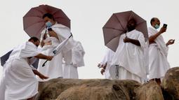 Jemaah haji menaiki Jabal al-Rahma (Gunung Rahmat) saat menunaikan prosesi wukuf di Padang Arafah, tenggara Kota Suci Mekah, Arab Saudi, Senin (19/7/2021). Ibadah haji tahun ini hanya diikuti oleh 60 ribu orang jemaah saja. (FAYEZ NURELDINE/AFP)