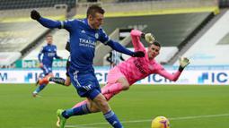 Striker Leicester City, Jamie Vardy melepaskan tendangan ke gawang Newcastle United yang dikawal Karl Darlow  dalam laga lanjutan Liga Inggris 2020/21 pekan ke-17 di St James'Park, Minggu (3/1/2021). Leicester City menang 2-1 atas Newcastle United. (AFP/Lee Smith/Pool)