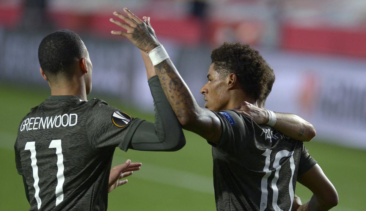Striker Manchester United, Marcus Rashford (kanan) melakukan selebrasi usai mencetak gol pertama ke gawang Granada dalam laga leg pertama perempatfinal Liga Europa 2020/2021 di Nuevo Los Carmenes Stadium, Granada, Kamis (8/4/2021). Manchester United menang 2-0. (AFP/Cristina Quicler)
