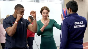 Duchess of Cambridge, Kate Middleton (tengah) diperlihatkan  gerakan Taekwondo oleh Lutalo Muhammad (kiri) dalam acara SportsAid di Stadion London, London timur, Rabu (26/2/2020). Dalam acara SportsAid, Kate Middleton ikut lari bersama dengan para atlet dan mencoba taekwondo. (Yui Mok/POOL/AFP)