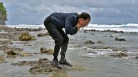 Sesampainya di bibir pantai, Jokowi jongkok mencuci tangan lalu membasuh mukanya dengan air laut, Sulawesi Utara (19/10). Dalam kunjungan kerjanya, Jokowi meresmikan beroperasinya Bandar Udara Miangas. (Agus Suparto)