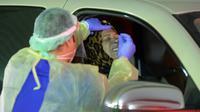 Petugas medis mengambil sampel usap dari seorang wanita di pusat tes COVID-19 lantatur (drive-thru) di Kegubernuran Farwaniya, Kuwait, 18 November 2020. Kuwait pada Rabu (18/11) melaporkan tambahan 452 kasus COVID-19 dan sembilan kematian baru. (Xinhua/Asad)